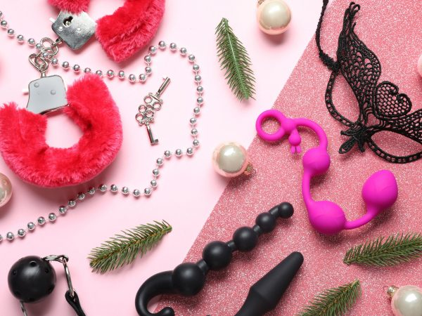 Set of different sex toys and Christmas decorations on pink background, flat lay