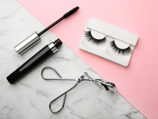 Artificial eyelashes and accessories on color background, flat lay