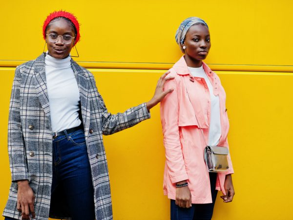 Two young modern fashionable, attractive, tall and slim african muslim womans in hijab or turban head scarf and coat posed against yellow bus.