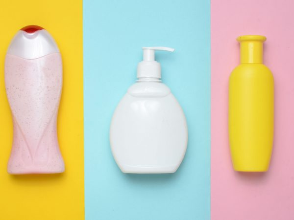 Bottles products for shower and bathroom on a multi-colored pastel background. Shampoo, liquid soap, shower gel. Top view. Flat lay. Minimalism trend.
