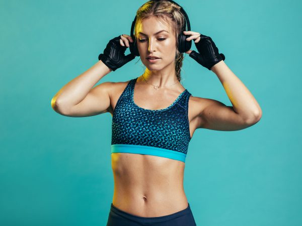 Muscular female with headphones on blue background. Fitness woman relaxing and listening music during her workout