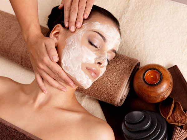 17642653 – spa massage for young woman with facial mask on face – indoors