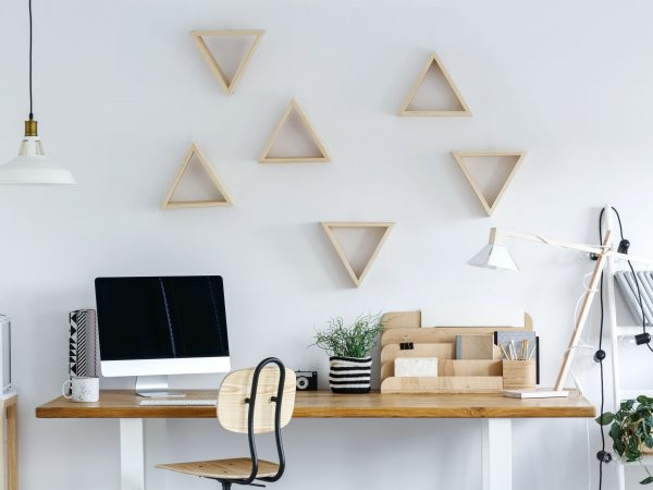 Wooden geometric frames on white wall in freelancer's room with plant in striped material pot