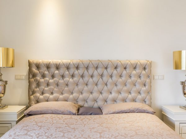 Close-up of double bed with quilted headboard and elegant night lamps
