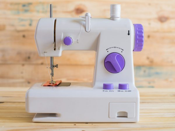 Modern sewing machine on wood table