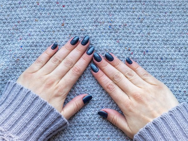 Female hands in gray knitted sweater with beautiful manicure – dark blue glittered nails on knitted background