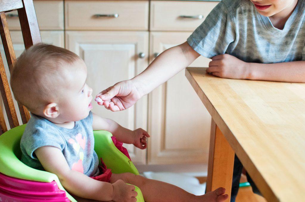 Madre alimentando a su bebe sentado en una trona