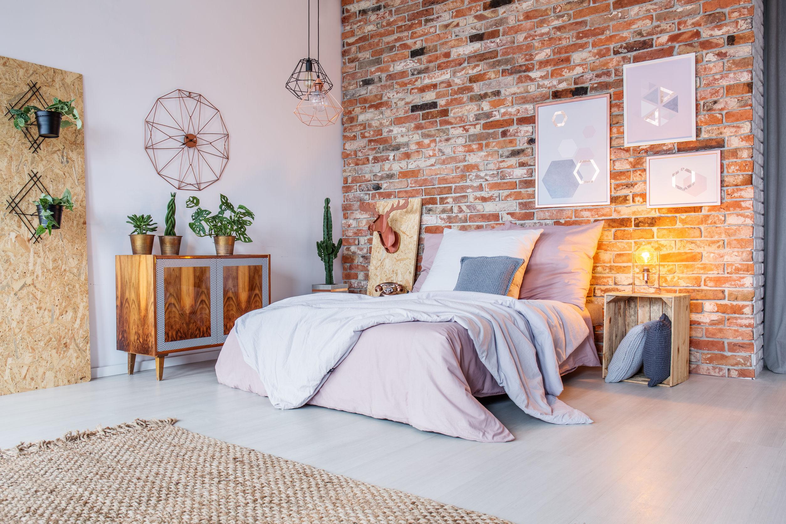 Dormitorio luminoso con cama doble, pared de ladrillo y alfombra