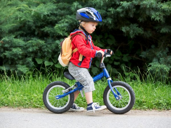 Cute toddler boy with blue helmet, riding balance bike on the street, blurred background