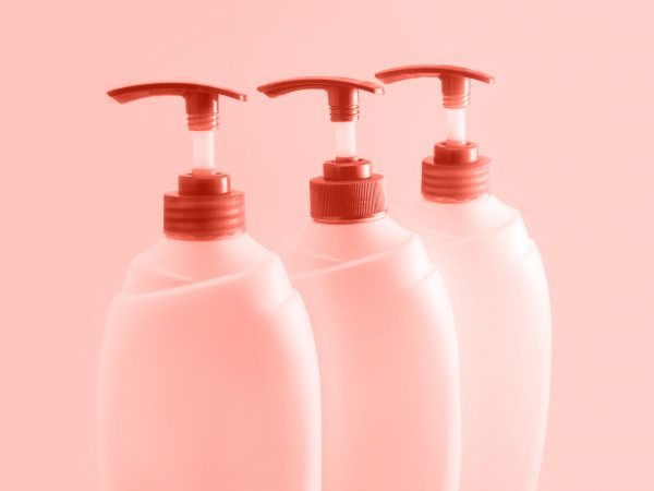 Three plastic bottles with dispenser on coral background. Cosmetics for body and hair