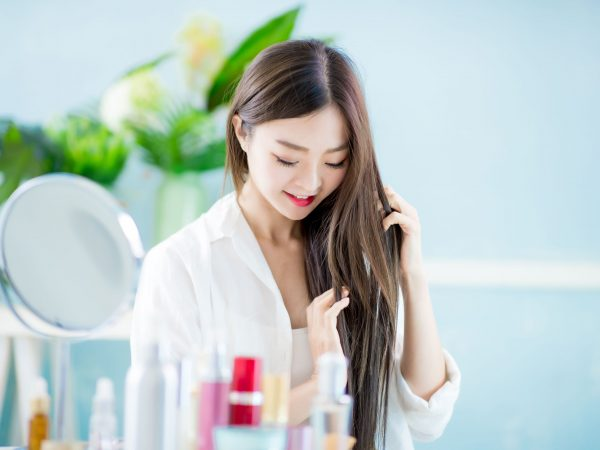 Beautiful asian woman applying oil onto hair with mirror at home