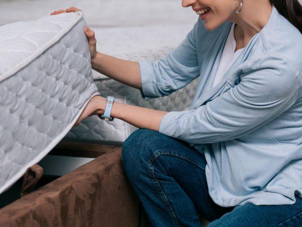cropped shot of smiling woman choosing orthopedic mattress in furniture store