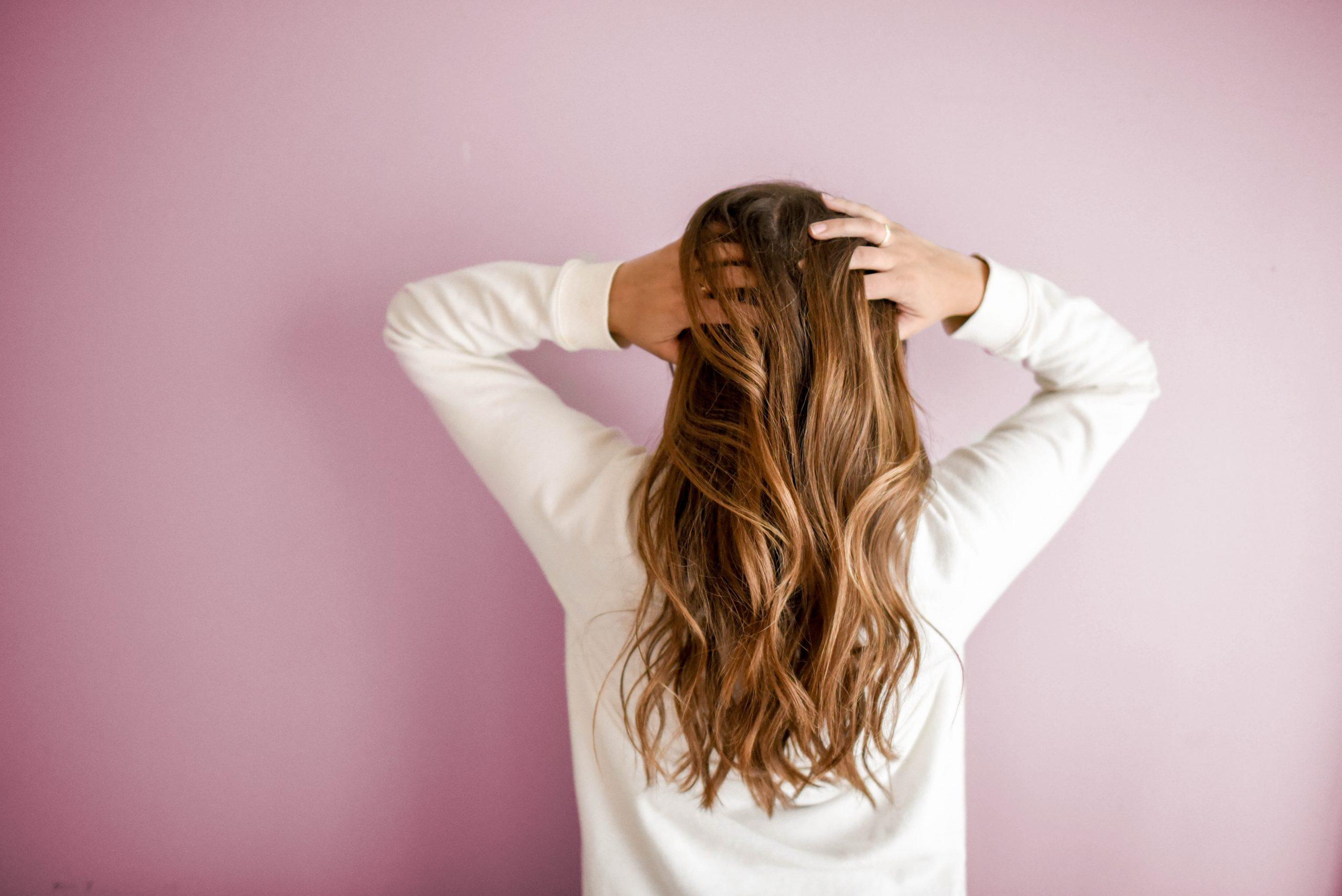Mujer de espaldas mostrando su cabello en fondo rosa