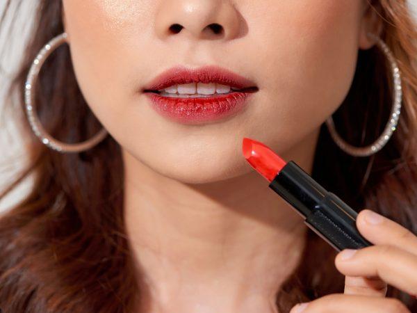 Beautiful model girl holding lipstick