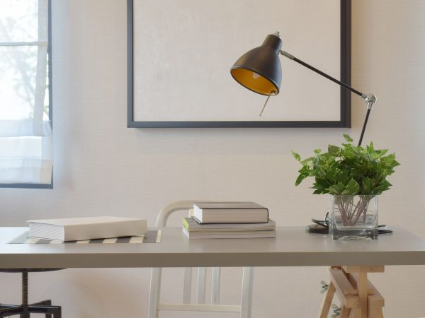 work table with book lamp, and vase at home
