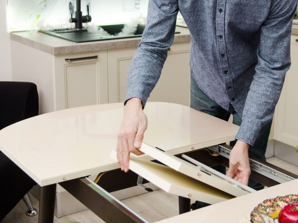man lays out a sliding glossy dining table on which stands a plate with artificial fruit.