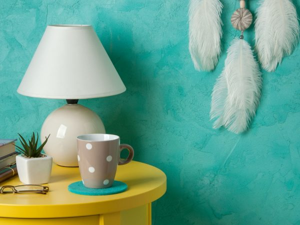 White gray dream catcher ,yellow bedside table , plant, lamp, mug in bedroom interior on aquamarine textured background. Bedroom decor