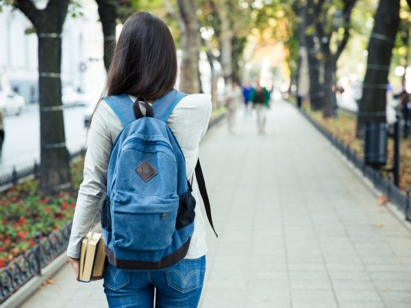 Back view portrait of a female student walking in the city park outdoors