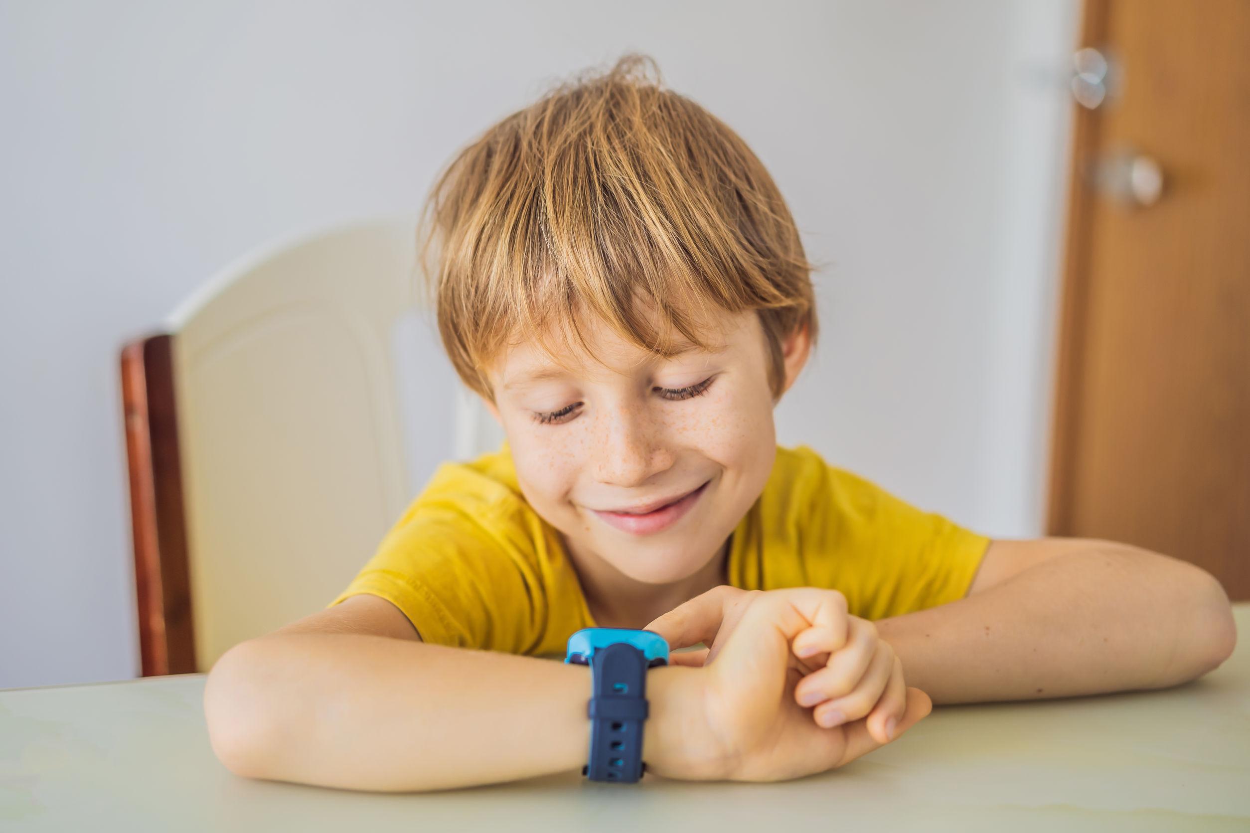 niño sentado en la mesa y mirando smartwatch.