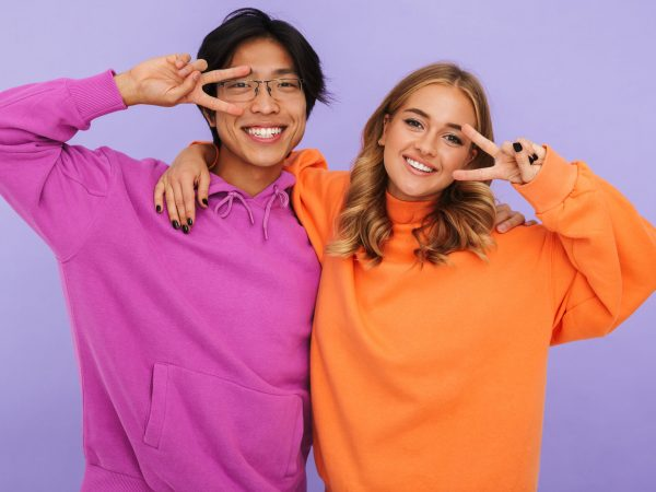 Photo of emotional young couple friends students standing isolated over white wall background showing peace gesture.