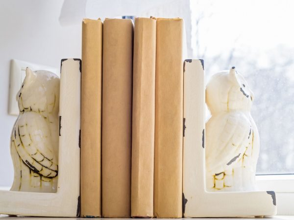 Close-up of old books on a plastic windowsill with beautiful white decorative bookrest