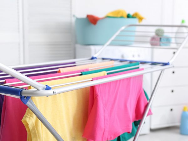 Clean laundry hanging on drying rack indoors, closeup