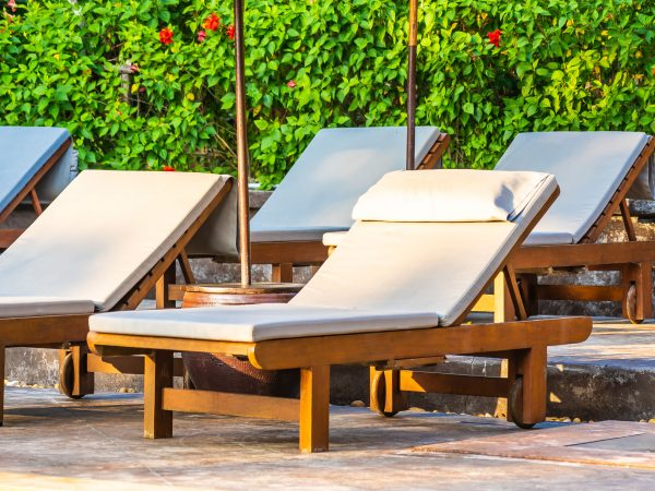 Umbrella and chair around swimming pool in hotel resort neary sea ocean beach for leisure vacation travel concept