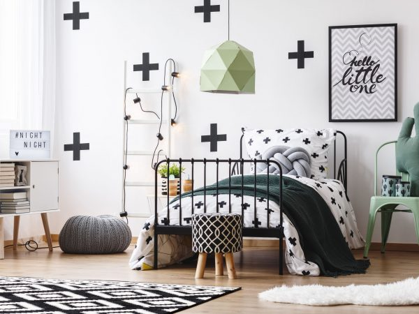 Chic green lamp above bed in crazy bedroom with pouf and cactus pillow on mint chair