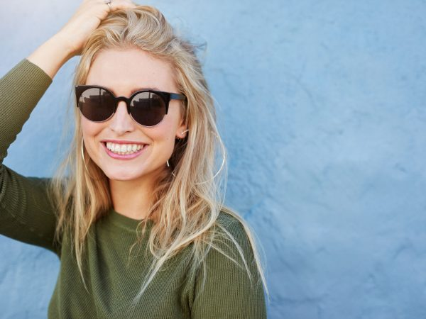 62293945 – close up shot of pretty young woman in sunglasses smiling. attractive young female model with copy space on blue background.