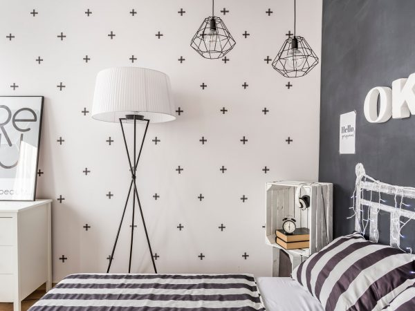 New style bedroom with chalkboard wall, pattern bedding and simple floor lamp