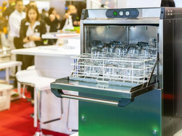 close up glass plate and tea cup or tumbler on basket in open automatic dishwasher machine for industrial