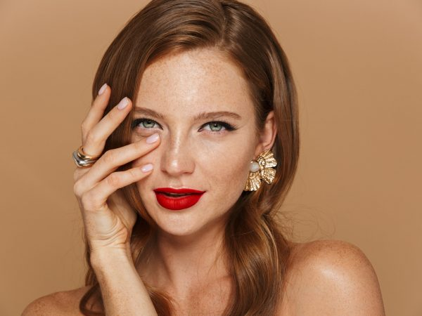Close up of a beautiful young woman wearing makeup and jewelry accessories posing isolated over beige background, holding hand at her face