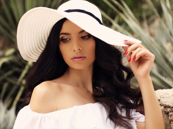 fashion outdoor photo of gorgeous woman with dark hair in elegant white dress and hat