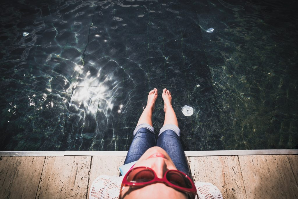 Mujer sentada a orilla de lago tomando el sol