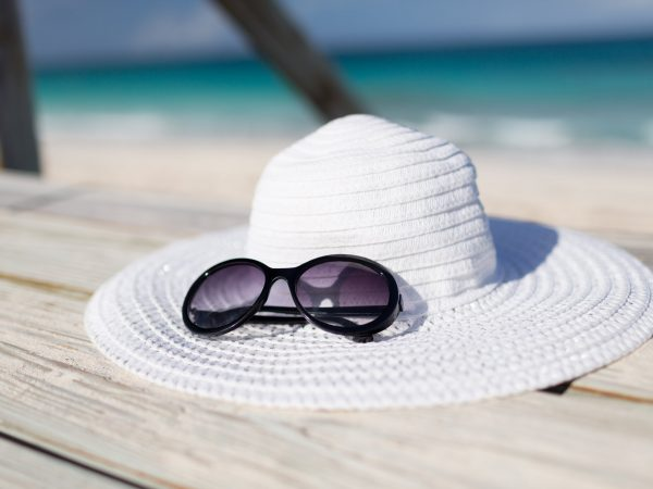 beach, summer, vacations and accessories concept – close up of beach accessories at seaside