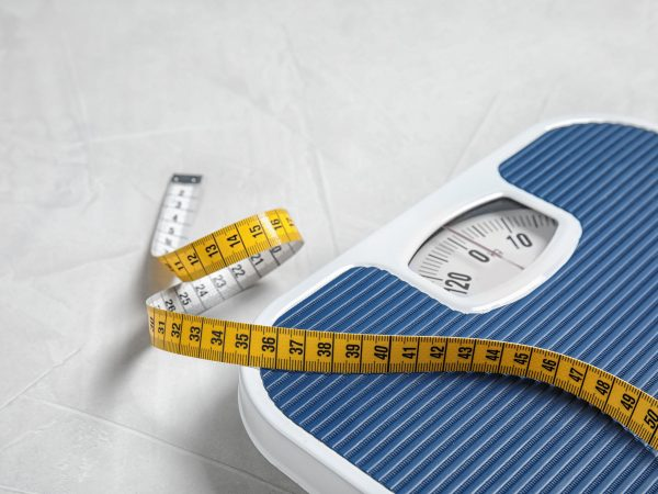 Scales and measuring tape on light background with space for text. Weight loss
