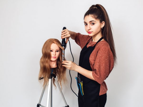 woman hairdresser student studying on mannequin head