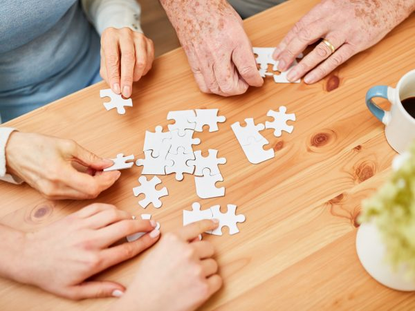 Wrinkled hands of seniors and young people playing puzzle together