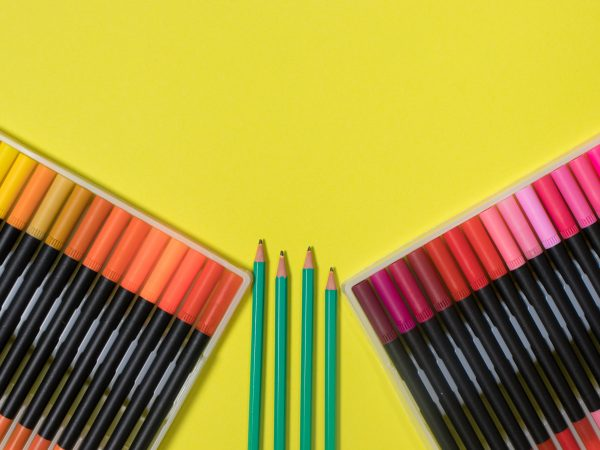 Colored felt-tip pens and pencils on a yellow background with a place for text top view. Bright banner for a stationery store