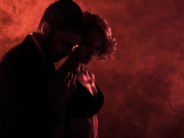Man tenderly hugging beautiful woman on red smoke background