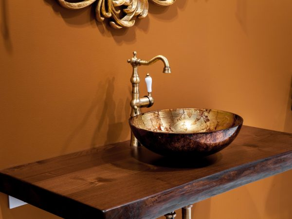 Retro style bathroom – detail view of ceramic bath sink with gold faucet